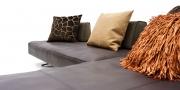 EASY -Detailbild der gewollt weichen Sitzfläche in braunen Leder mit passenden Dekokissen